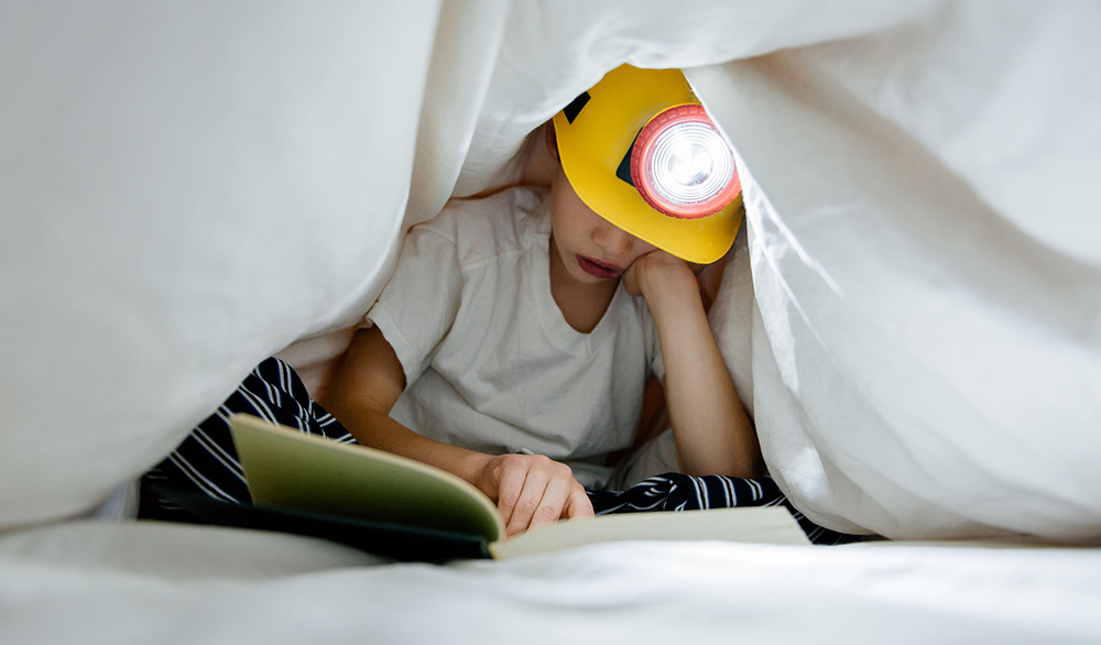 kid reading under covers
