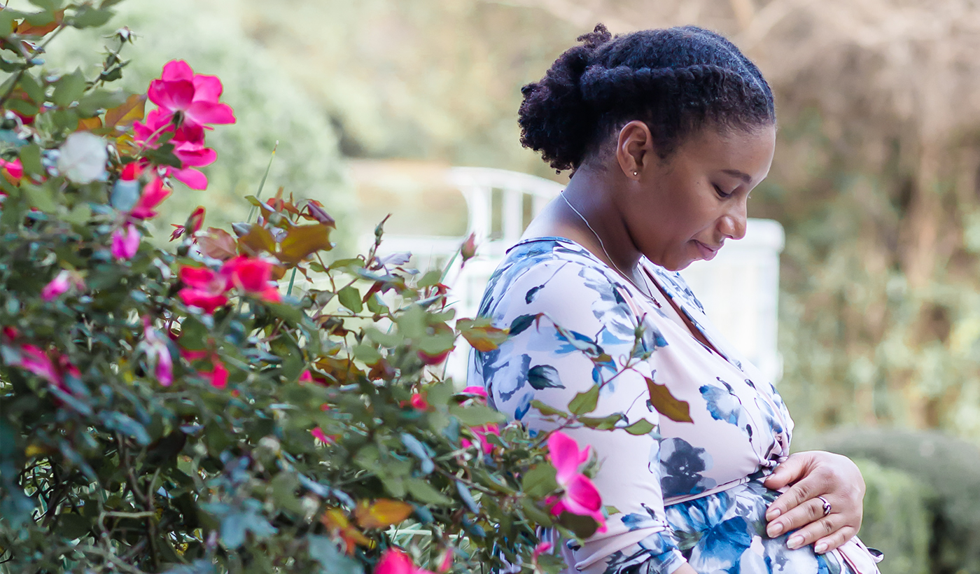 A pregnant woman surrounded by flowers